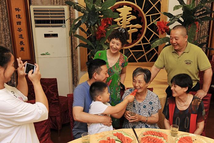 شن زوئان 84 ساله (ردیف جلو، از راست دوم) در یک دورهمی با اعضای خانوادهاش در مرکز ارشد جیوان در ناحیه نانچونِ شهر هوژوِ استان ژجیانگ در شرق چین به تاریخ 13 سپتامبر 2019. (شینهوا/تان جین)