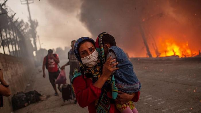 مادری با فرزندش در حال فرار از آتشسوزی اردوگاه موریا در یونان/ عکس: Aznews TV