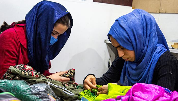 شرکت تولیدی لباس «جامه دیزاین» متعلق به زنان، لباسهای افغانی را در داخل و خارج افغانستان میفروشد و فرصتهای شغلی را برای زنان مانند این دو کارگر فراهم میکند. عکس از مریم عالمی/FES